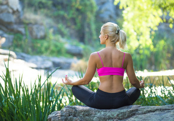 Beautiful young woman doing yoga in summer nature near river