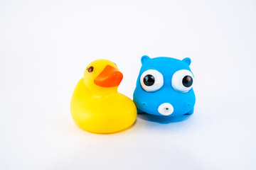 Isolated squeeze bath toys, plastic duck and hippo.