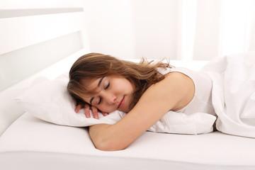 Junge Frau schläft im Bett mit Arm unter Kissen