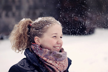 Curly girl in scarf among falling snow