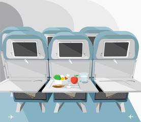Airplane seats with opened tables, food and drink