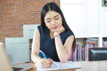 Beautiful Asian woman writing a notebook on table with laptop aside