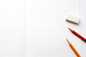 Blank notebook with pencil, red pencil, and eraser on white background.