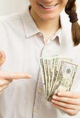 Woman hands holding dollar bills showing success