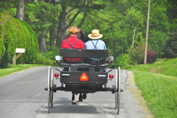 Lancaster County, Pennsylvania: Amish father wearing traditional straw hat and his son driving their open horse and buggy along a country road - Xu Lei Photo