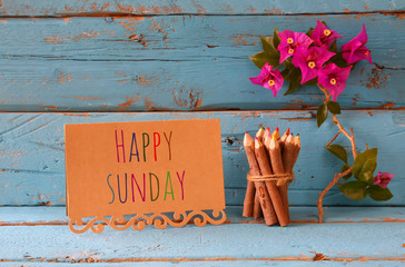 vintage card with phrase: happy sunday and stack of wooden colorful pencils on wooden texture table next to purple bougainvillea flower.