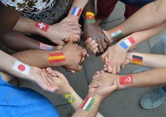 Internationale Brüder und Schwestern mit unterschiedlichen Flaggen auf ihren Armen gemalt stehen miteinander im Kreis und halten sich die Hände.