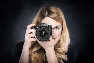 Photographer woman holding camera.