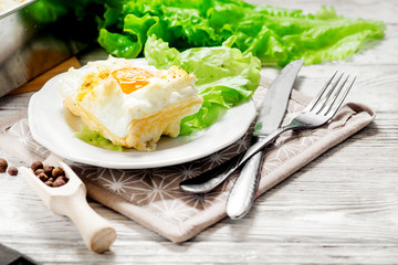 breakfast or lunch , air , beaten egg and baked in the oven , with lettuce and herbs on a white wooden background
