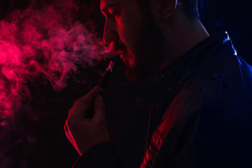 well-dressed bearded man smoking electronic cigarette in studio