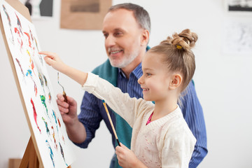Skillful old artist is teaching the child