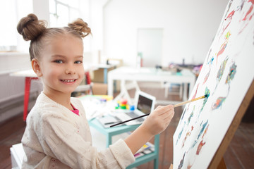 Cheerful little kid is painting with joy