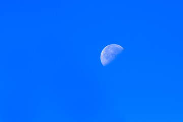 the white moon visible on a clear sky blue day