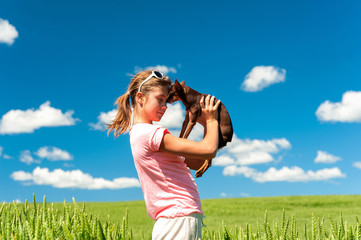 Young cheerful teenage girl in wheat field with her favorite dog