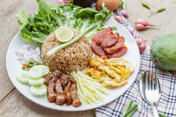 Rice maxed with shrimp paste is Thai Food ingredients are rice, shrimp paste, shallots, chili, fried egg, sweet pork, cucumber, sausage and mango.