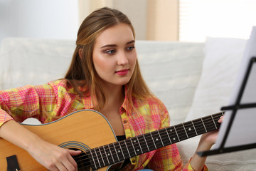 Beautiful smiling woman holding and playing western acoustic gui