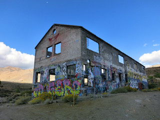 Abandoned shell of a building with painted color exterior - landscape color photo