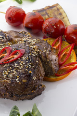 beef steak served with tomatoes and sesame  on a white plate