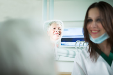 Old woman visiting the dentist taking care of her teeth.Young female dentist showing a granny her teeth,reflection in the mirror.Dentist doctor talking to a senior woman patient.Dental care for elder