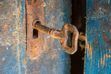 Old rusty key and keyhole on a blue wooden door