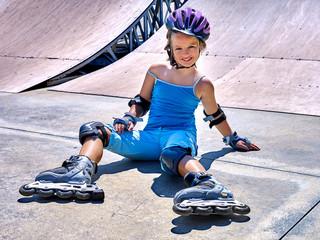 Girl wearing roller skates and helmet sitting on ride in skatepark.