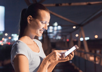 Young happy woman using her smartphone in a night time setting.