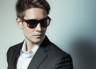 High fashion portrait of male model wearing sunglasses.