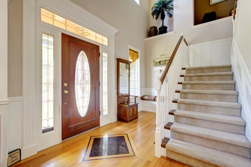 Nice entryway to home with carpeted staircase, and white interio