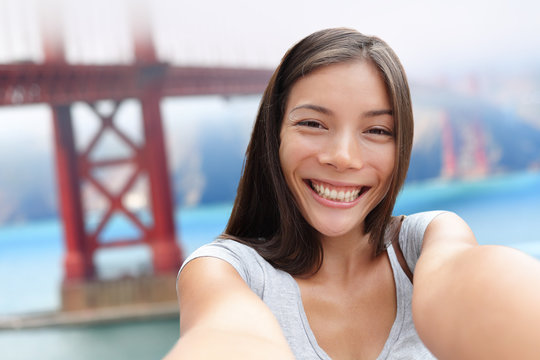Selfie girl on San Francisco Golden bridge travel. Cute young Asian woman adult taking picture with her smartphone during summer vacation in front of the famous American attraction, California, USA.