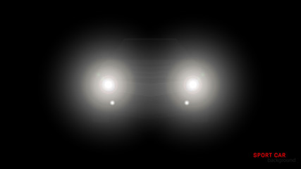 Silhouette of car with headlights on black background