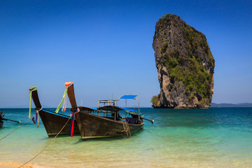 Long tail boat on the beautiful beach and beauty blue sky , poda
