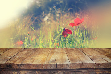 wooden rustic table in front of red poppies against sky with light burst. vintage filtered image. product display and picnic concept