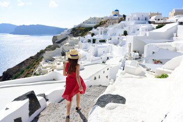 Wall Mural - Santorini travel tourist woman on vacation in Oia walking on stairs. Person in red dress visiting the famous white village with the mediterranean sea and blue domes. Europe summer destination.