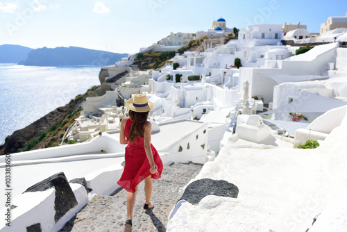 Wall mural Santorini travel tourist woman on vacation in Oia walking on stairs. Person in red dress visiting the famous white village with the mediterranean sea and blue domes. Europe summer destination.
