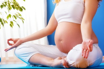 Pregnancy yoga. Young pregnant woman doing yoga at home.