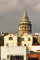 One of the symbols of Istanbul city, aesthetic and beautiful Galata Tower behind other unaesthetic buildings