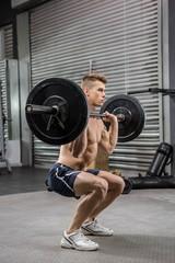 Shirtless man lifting barbell