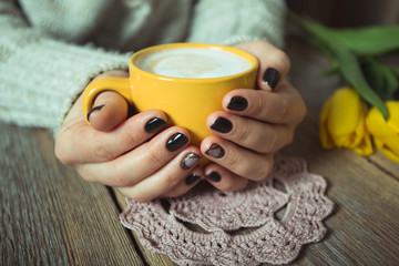 Yellow cup in the hands of women. Gel nail manicures. Phone and