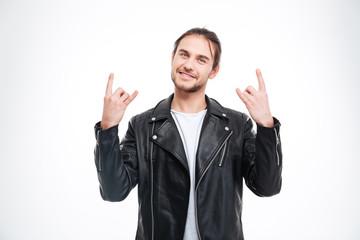 Smiling handsome man in black leather jacket doing rock gesture