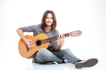 Smiling young man sitting on the floor and playing guitar