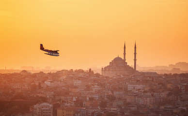 Turkey, Istanbul. Seaplane flying over the city with a view of the mosque.