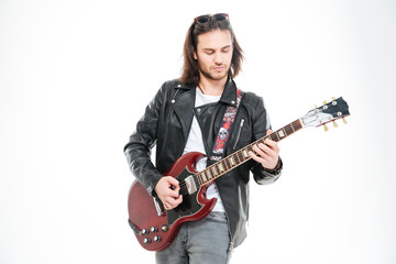 Serious young male guitarist standing and playing electric guitar