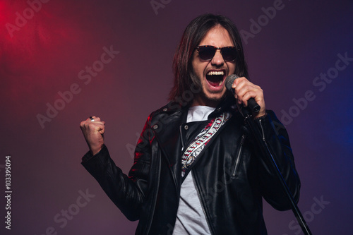 """Attractive Young Male Singer With Long Hair Singing Using ..."