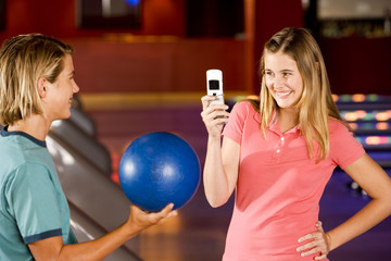Teenage boy and girl in a bowling alley, girl taking a picture