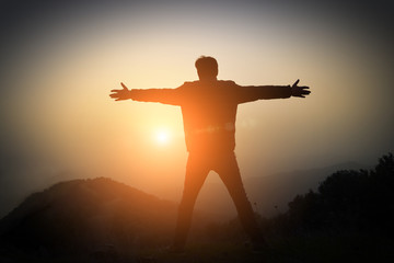 man with arms raised at sunset in the mountains