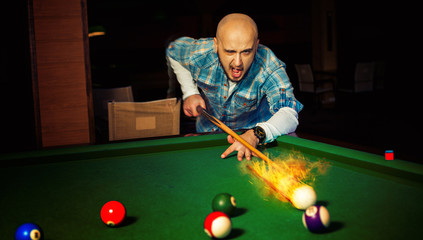 horizontal photo angry man hits fireball at pool billiard