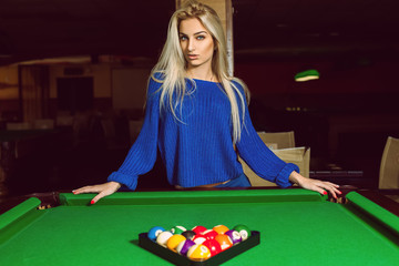 Lovely adult blonde posing near a billiard table with a pyramid