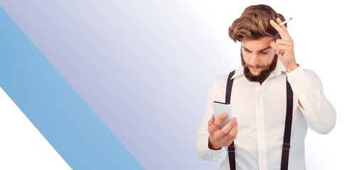 Composite image of a hipster looking at a mobile phone