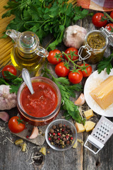 tomato sauce and ingredients on a wooden background, top view
