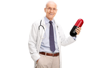 Mature doctor holding a large pill